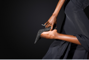 woman-wearing-black-ballgown-and-putting-heels-on